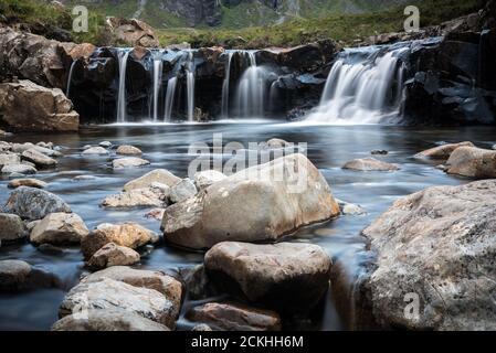 Fairy piscinas cascadas rodeadas de montañas durante un día nublado en la Isla de Skye en Escocia