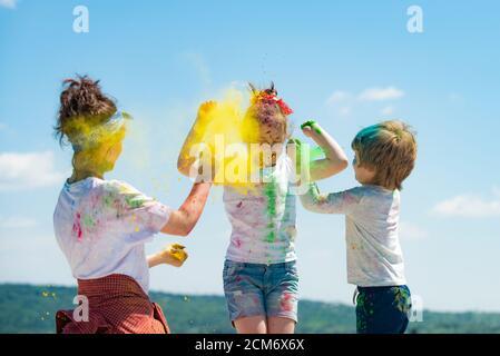 Colores brillantes de verano. Grupo de niños disfrutando jugando con polvo de colores y salpicaduras de polvo de colores. Foto de stock