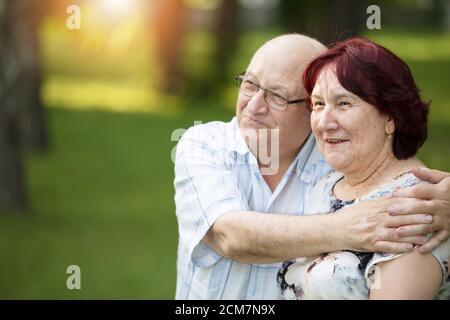 Feliz pareja de ancianos en una caminata. Guapo hombre y mujer ancianos. Marido y mujer de edad avanzada en el fondo de la naturaleza. Foto de stock