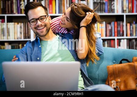Pareja relajándose juntos en el sofá con el PC de ordenador divirtiéndose.