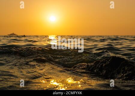 las olas del mar se cierran a la hora de la puesta del sol con el sol rojo y anaranjado reflejos en el agua. naturaleza resumen bl Foto de stock