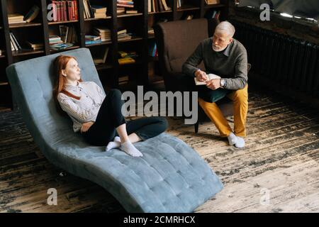 Atractiva mujer joven en el sillón hablando de sus problemas con el hombre maduro psicoterapeuta