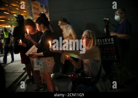 Los partidarios del anti-Trump mantienen velas después de una manifestación de Donald Trump en Phoenix, Arizona, EE.UU., el 22 de agosto de 2017. REUTERS/Sandy Huffaker Foto de stock