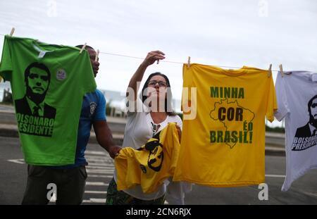 Una mujer toma una camiseta con la imagen del nuevo presidente electo de Brasil, Jair Bolsonaro, frente al condominio de Bolsonaro en el barrio barra da Tijuca en Río de Janeiro, Brasil 29 de octubre de 2018. REUTERS/Pilar Olivares