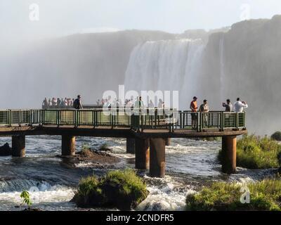 Turistas en plataforma de observación en las Cataratas del Iguazú (Cataratas do Iguacu), Patrimonio de la Humanidad de la UNESCO, desde el lado brasileño, Paraná, Brasil Foto de stock