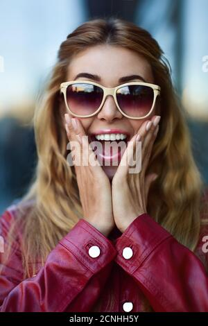 Primer plano retrato de una hermosa chica sonriente en gafas de sol con buenos dientes divertirse en la calle.