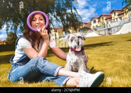 Mujer caucásica alegre jugando con su amado perro en el parque. El concepto de amor a los animales. Mejores amigos. Perro raza Schnau