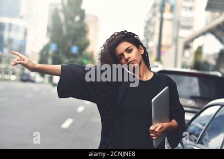 Una mujer seria de raza mixta usa un teléfono, intenta tomar un taxi. Imagen filtrada