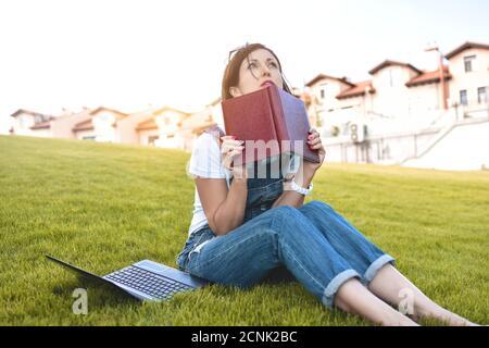 Retrato de una bonita mujer adulta sentada en el césped verde en el parque con un portátil en las piernas, pasando el día de verano trabajando al aire libre, usando la