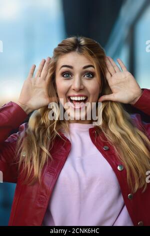 Primer plano retrato de una hermosa chica sonriente con buenos dientes divirtiéndose en la calle.