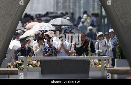 La gente ruega por las víctimas frente al cenotafio por las víctimas del bombardeo atómico de 1945, en el Parque Conmemorativo de la Paz en Hiroshima, Japón occidental, el 6 de agosto de 2015, en el 70º aniversario del primer bombardeo atómico del mundo. Las campanas se pusieron en marcha y miles se inclinaron en oración en Hiroshima el jueves en ceremonias que marcaron el 70º aniversario del primer bombardeo atómico del mundo y pusieron de relieve las crecientes tensiones por los movimientos de Japón fuera de su constitución pacifista. REUTERS/Toru Hanai