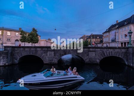 Copenhague, Dinamarca - 26 de agosto de 2019: Personas a bordo de un yate navegando al atardecer a lo largo del puente de tormenta ( Stormbro ) con el Museo Nacional ( Prince's Mansi