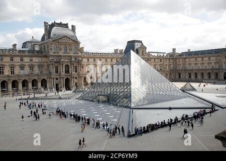 Los visitantes hacen cola para entrar en la Pirámide del Louvre diseñada por el arquitecto estadounidense nacido en China Ieoh Ming Pei en París mientras el museo reabre sus puertas al público después de casi 4 meses de cierre debido al brote de la enfermedad coronavirus (COVID-19) en Francia, 6 de julio de 2020. REUTERS/Charles Platiau