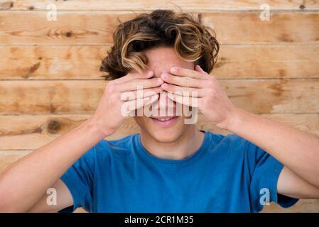Joven adolescente caucásico ocultar sus ojos y sonreír - joven y el concepto de la generación z adolescente con hombre feliz y agradable niño con camiseta azul y madera