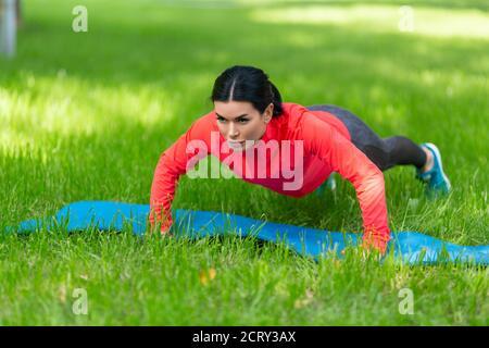Mujer en forma haciendo ejercicios de empuje en el parque.