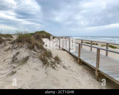Paseo marítimo de madera cerca de las dunas de arena en Costa Nova, Portugal con el océano en el fondo Foto de stock