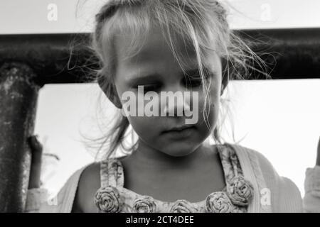 Primer plano retrato en blanco y negro de un niño caucásico triste y resentido. Las emociones sinceras de los niños. Momentos de la infancia. Niño en la naturaleza.