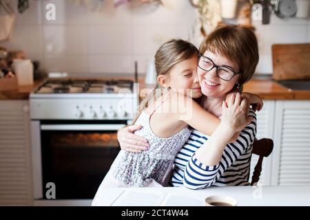 Feliz madre está abrazando a su hija en la acogedora cocina de casa. La mujer y la niña linda están sonriendo.