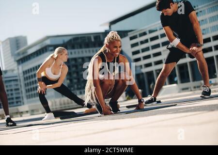 Grupo de personas haciendo ejercicio juntos al aire libre en la ciudad. Multiética hombres y mujeres en el deporte haciendo ejercicios de estiramiento.