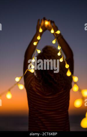 Luces mágicas y personas para el concepto de sueños - puesta de sol y colores hermosos - mujer con luces para orar o. disfrutar de la vida