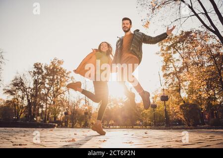 Vista de ángulo bajo foto completa de dos jóvenes alegres gente chica tipo tener la mano salto en otoño de octubre ciudad parque