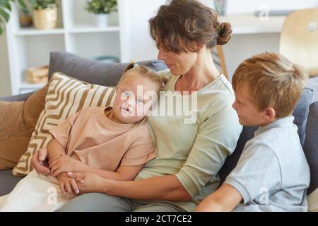 Retrato de la madre moderna abrazando a la niña con síndrome de Down mientras sentado en el sofá con dos niños en el interior de la casa Foto de stock