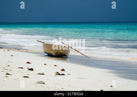 Pequeño barco en la costa de la playa con tormenta en el fondo
