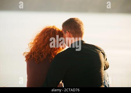 Una pareja joven y agradable sentada al lado de la otra con tiempo juntos cerca de un río.
