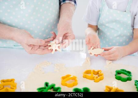 Vista de primer plano recortada de buenas manos abuelo preparación de la cocina galletas dulce aperitivo utilizando cortador forma animal forma ayuda figura asistencia en