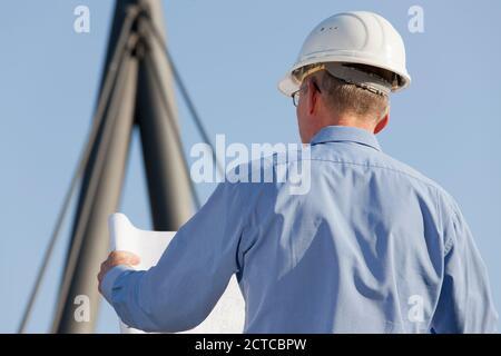 Arquitecto o ingeniero leyendo un plan de construcción delante de fondo industrial - enfoque en la cabeza