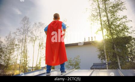 Boy está jugando un papel de Super Hero. Está de pie sobre un techo de una casa con sus manos en la cintura. El joven lleva un cabo rojo brillante. Lo es