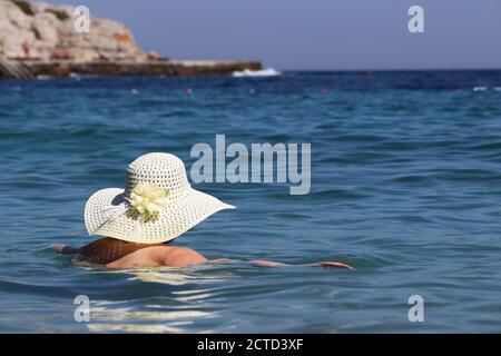 Mujer en sombrero de sol nadando en el mar azul sobre rocas de fondo. Relajación en el agua, vacaciones en la playa