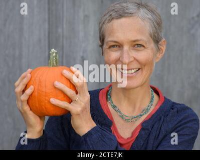 La mujer de raza blanca canadiense de mediana edad con pelo corto sostiene una calabaza en sus manos y sonríe ante la cámara.