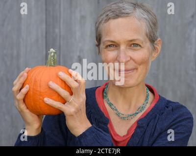 La mujer canadiense caucásica de mediana edad con pelo corto sostiene una calabaza en sus manos y mira la cámara.