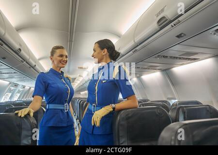 Dos tripulantes de cabina esperando a los pasajeros