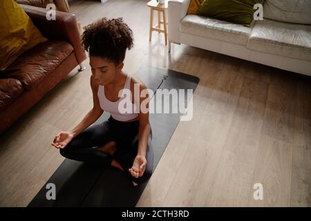Vista de gran ángulo de la joven africana en posición de loto practicar meditación y ejercicio de respiración en casa