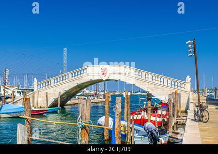 Puente de piedra Ponte di Vigo a través del canal de agua vena con coloridos barcos cerca del terraplén del muelle en el centro histórico de la ciudad de Chioggia, cielo azul de fondo en el día de verano, Región Veneto, Norte de Italia