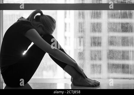Tristeza y desesperación - deprimida joven sentada sola en casa por la ventana con vista a la ciudad. Blanco y negro.