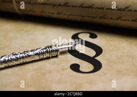 Primer plano de párrafo aislado en papel de la época con pluma de tinta retro de plata y documento de texto (centrado en la punta de la pluma de tinta, el texto es autohecho)