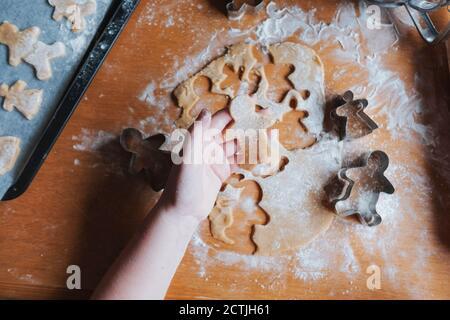 Vista superior de una chica que sostiene a un hombre de pan de jengibre sin cocinar