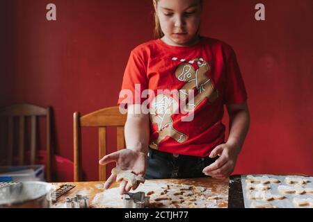 Vista frontal de una chica que sostiene a un hombre de pan de jengibre sin cocinar en su mano