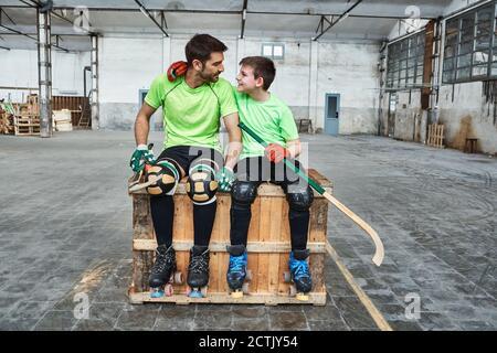 Niño sonriente con brazo alrededor del padre mientras se sentaba con hockey palos en la caja de madera en la cancha