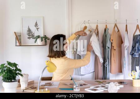 Joven diseñadora de moda mirando la ropa colgando del estante en la tienda