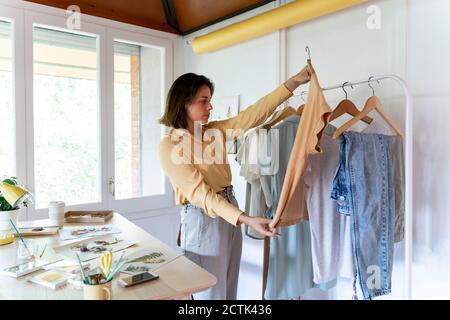 Confidente joven diseñadora de moda examinando la cima mientras que está parado adentro almacenar