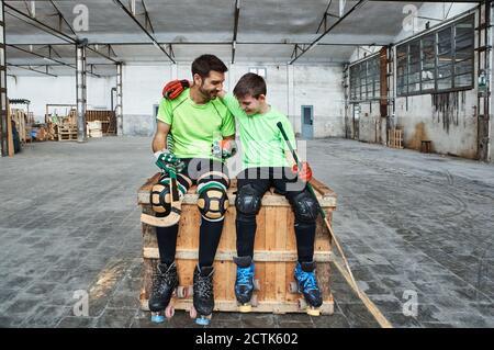 Niño feliz con el brazo alrededor del padre mientras se sentaba con hockey palos en la caja de madera en la cancha