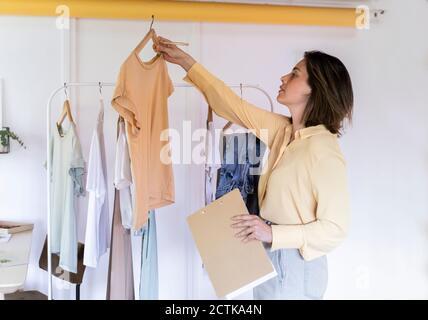 Diseñador de moda confidente que examina la parte superior mientras está de pie con el portapapeles en almacenar