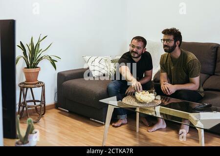 Amigos masculinos viendo deportes en la televisión mientras se sienta sobre el sofá en la sala de estar