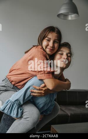 Juguetón chica soplando goma de burbujas mientras piggybacking amigo contra la pared en casa