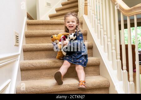 Chica de 2.5 años jugando con animales rellenos en la escalera, cuidadosamente sacando su camino hacia abajo (MR)