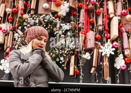 Un retrato de una joven hermosa mujer ora en la calle de Navidad, Navidad. Foto de stock